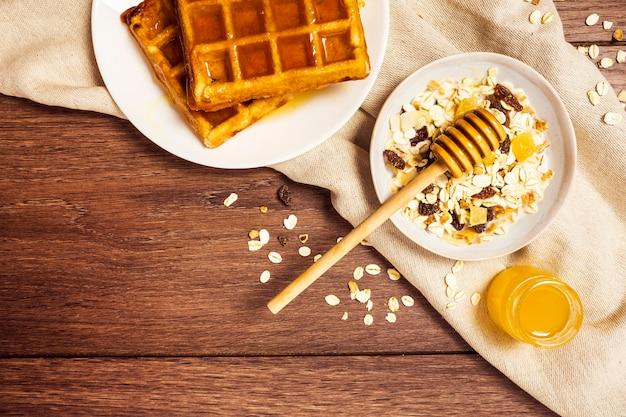 健康的なオート麦と木製のテーブルの上に蜂蜜とおいしいワッフル 無料写真