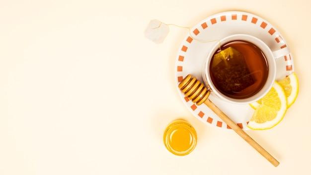 有機レモンスライスとベージュを背景に蜂蜜とお茶のカップ 無料写真