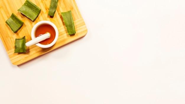 Кусочек меда и алоэверики на деревянной разделочной доске на белом фоне Бесплатные Фотографии