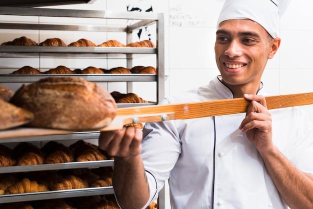Улыбающийся мужчина-пекарь в погонах вынимает с лопатой свежеиспеченный хлеб из духовки Бесплатные Фотографии