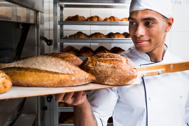 オーブンから焼きたてのパンを木製のシャベルで取り出す若い男性ベイカー 無料写真