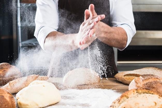焼きたてのパンと木の机の上に小麦粉を散布男性のパン屋さんの手のクローズアップ 無料写真