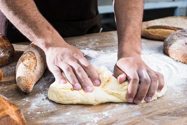 テーブルの上の生地を混練男性のパン屋の手のクローズアップ 無料写真