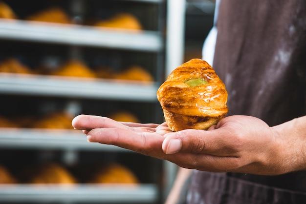 焼きたての甘いパフペーストリーを持っている男性のパン屋さんの手のクローズアップ 無料写真
