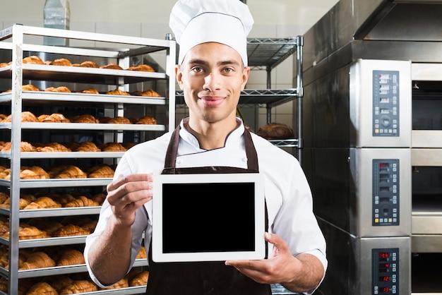 Усмехаясь портрет мужского хлебопека в форме держа малую пустую цифровую таблетку на хлебопекарне Бесплатные Фотографии