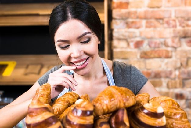 Удовлетворенная женщина-пекарь смотрит на свежеиспеченный круассан Бесплатные Фотографии