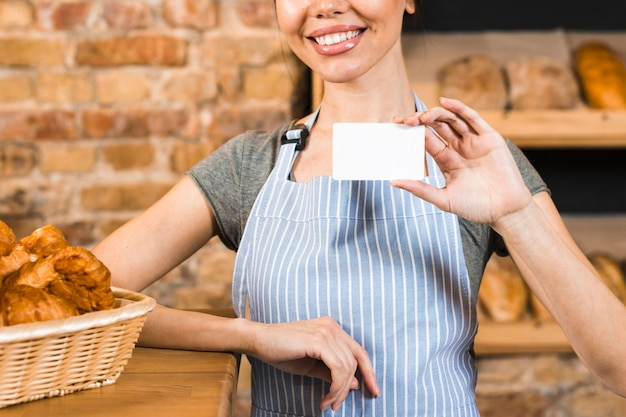 パン屋さんの白い訪問カードを示す若い女性ベイカーの笑みを浮かべてください。 無料写真