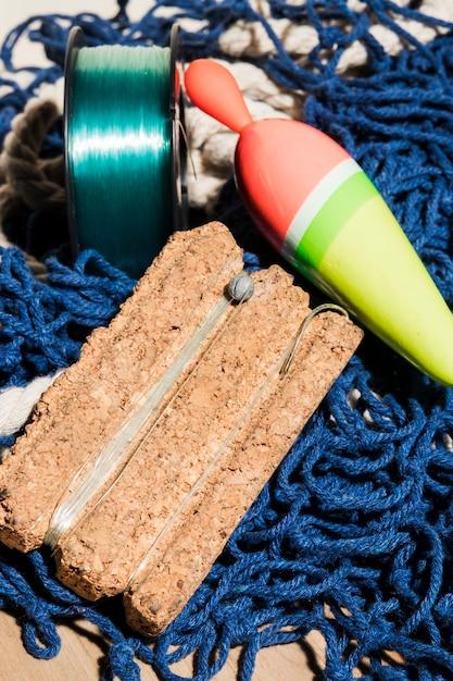 青い漁網の上コルクボード上のフロートと釣り糸を釣り 無料写真