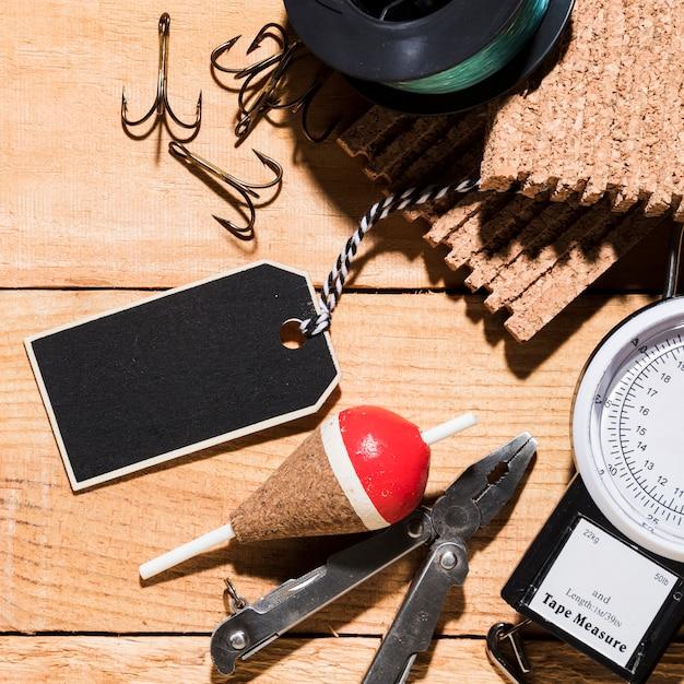 Пустой тег; крюки; рыболовный поплавок; плоскогубцы; пробковая доска; рыболовная катушка и измерительный инструмент на деревянный стол Бесплатные Фотографии