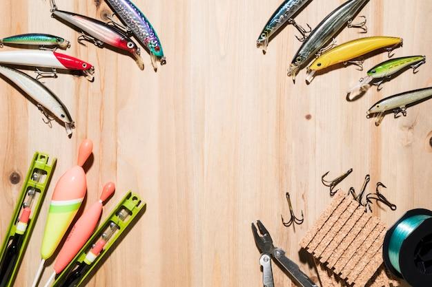 釣りルアーで作られたフレーム。フロート釣りプライヤー木製の背景上のフック 無料写真