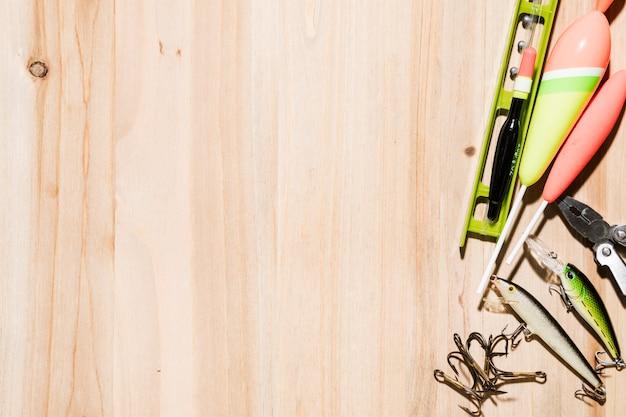 フィッシュボバーフック;釣りのルアー。釣り糸と木製の机の上ペンチ 無料写真