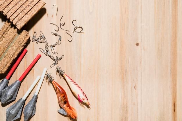 Крупный план рыболовного крючка; рыболовные приманки; пробка с леской и грузилами на деревянном фоне Бесплатные Фотографии