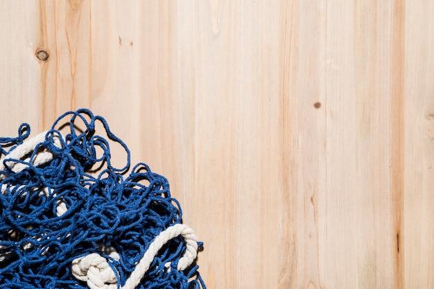 木製の背景に青い漁網 無料写真