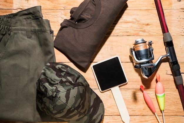 空白の小さなプラカード。釣りフロート。釣り竿と木製の机の上の男性服 無料写真
