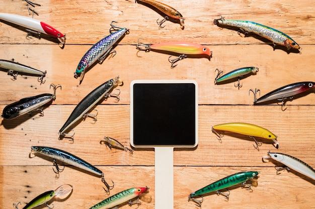 木製の机の上のカラフルな釣りのルアーに囲まれた空白の黒いプラカード 無料写真