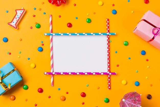 ギフト用の箱と黄色の背景にカラフルな菓子で飾られた空白のカード 無料写真