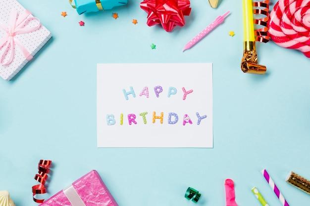 青い背景上のアイテムで飾られたお誕生日おめでとうカード 無料写真