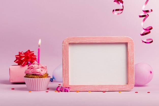 ピンクの背景に白いフレームスレートとマフィンの上に火をつけたキャンドル 無料写真