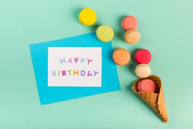 ミントグリーンの背景にお誕生日おめでとうカードの近くのマカロンとワッフルコーン 無料写真