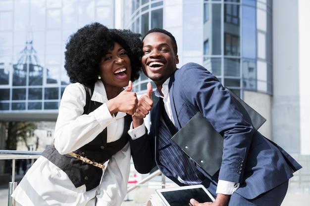 幸せなアフリカの若い男と親指を現して女性の肖像画 無料写真