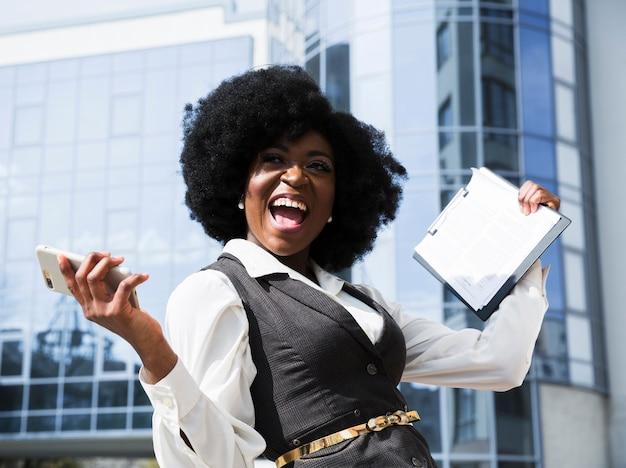 携帯電話とクリップボードを持って興奮している若いアフリカの実業家 無料写真