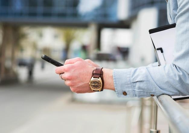 携帯電話を使用してエレガントな腕時計を持ったビジネスマンの手 無料写真