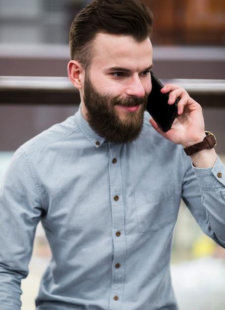 携帯電話で話している笑顔のひげを生やした若い男の肖像 無料写真