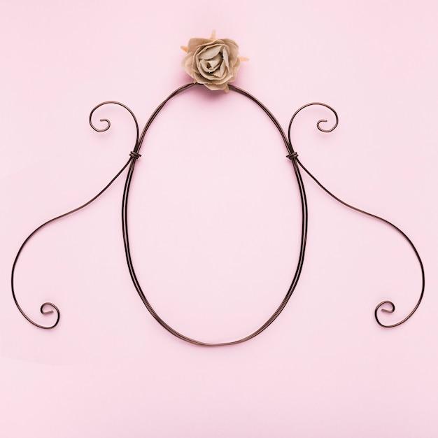 Рамка овальной формы с искусственной розой на розовом фоне Бесплатные Фотографии