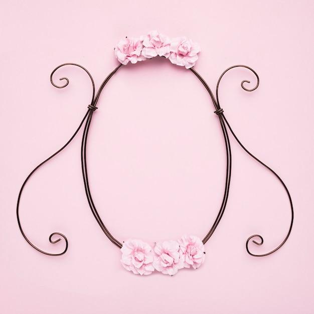 ピンクの壁にバラで装飾的な空のフレーム 無料写真