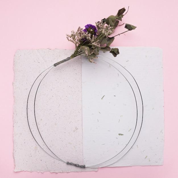 ピンクの背景の紙の上の丸いリングに花の花束 無料写真