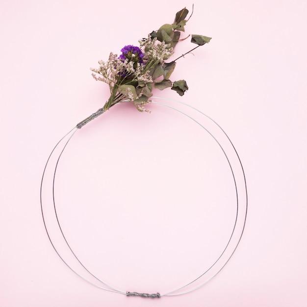 ピンクの背景のフレームの金属ワイヤーリングに縛ら花の花束 無料写真