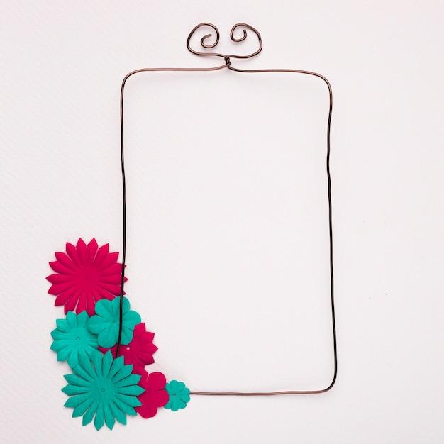白い背景に手作りの青とピンクの花で飾られた空の有線フレーム 無料写真