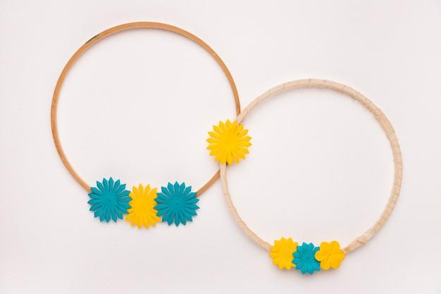 白い背景の上の黄色と青の花で飾られた円形の木製フレーム 無料写真