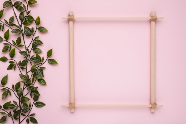 ピンクの背景に人工の緑の葉を持つ木製の正方形のフレーム 無料写真