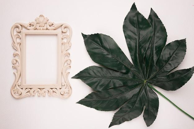 白い背景に緑の人工の葉の近くの木彫りのフレーム 無料写真