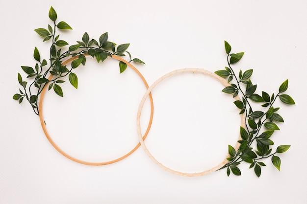 白い背景の上の緑の葉と木製の円形フレームを接続 無料写真