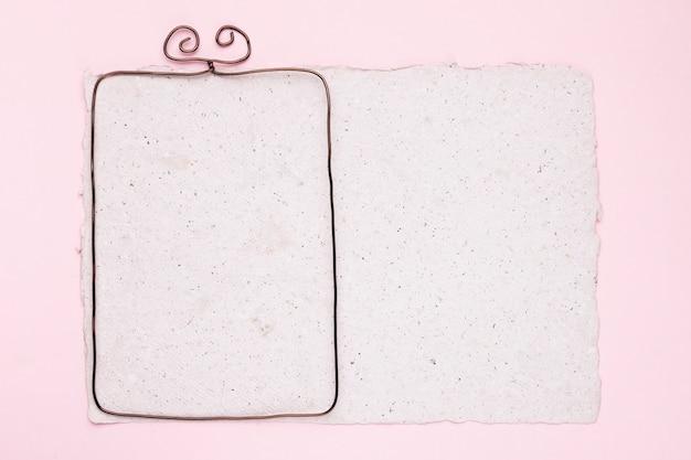 ピンクの背景の上の白いテクスチャ紙の上の金属フレーム 無料写真