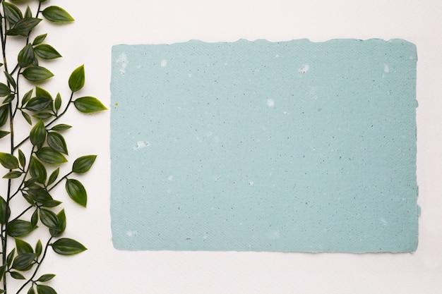 白い背景の空白の青いテクスチャ紙の近くの人工の緑の植物 無料写真