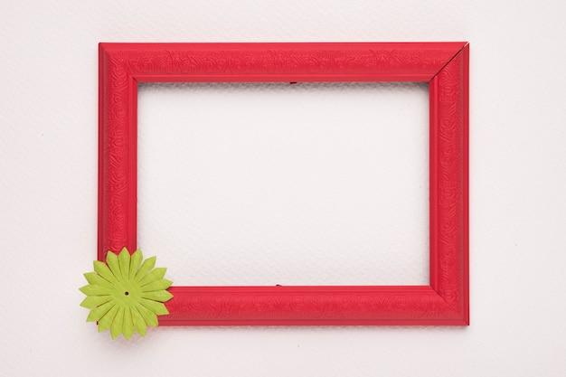 Красная деревянная рамка с зеленым цветком на белой стене Бесплатные Фотографии