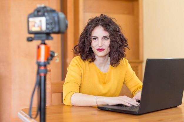 ブルネットのブロガーがラップトップに書く 無料写真