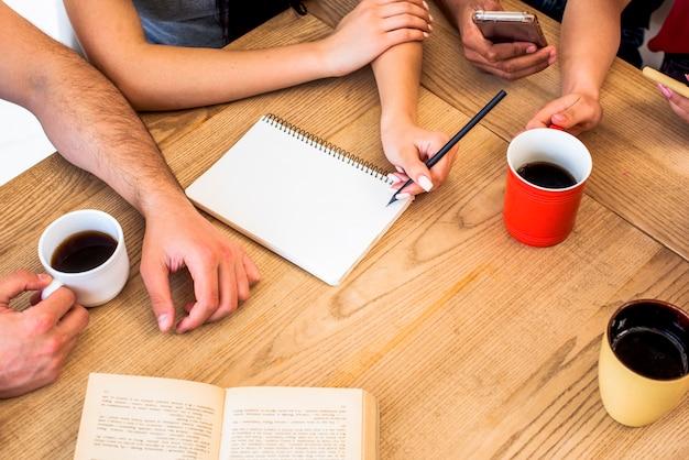木製の質感のあるテーブルの上の研究材料とコーヒーのカップを持つ学生の立面図 無料写真