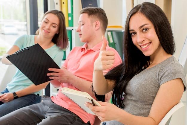クリップボードを保持している彼女の友達のそばに座ってジェスチャー親指を示す笑顔の女性 無料写真