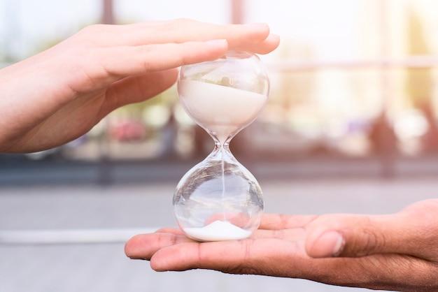 砂時計を持っている人の手のクローズアップ 無料写真