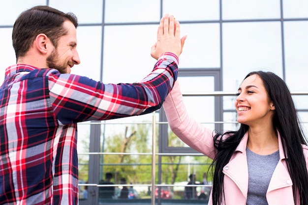 ガラスの建物の近くのハイタッチを与える若い幸せな男と女の友達 無料写真