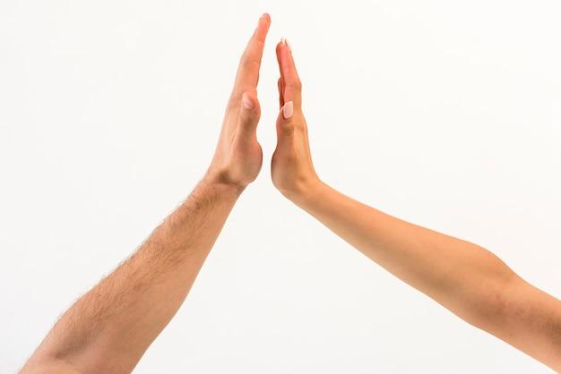 白い背景で隔離に対してハイファイブを与えるカップルの手のクローズアップ 無料写真