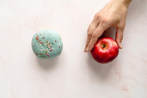 白い背景に対してドーナツの上にリンゴを選ぶ人 無料写真