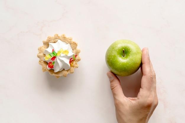 背景にタルトケーキの近く青リンゴを持っている人間の手 無料写真