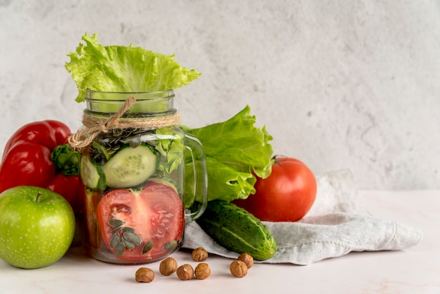 フルーツとヘーゼルナッツの石工の瓶に新鮮な健康野菜のスライス 無料写真