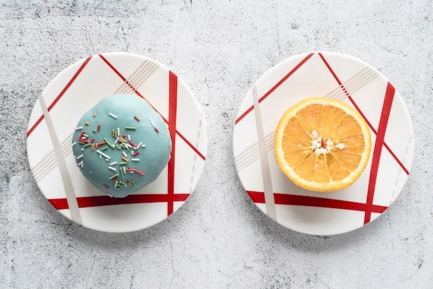ドーナツと半分にオレンジ色のコンクリートの背景の上皿にハイアングル 無料写真
