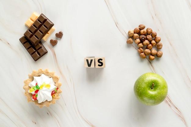 不健康なクリーミータルト。チョコレートと健康的なヘーゼルナッツ。テクスチャ背景上のリンゴ 無料写真